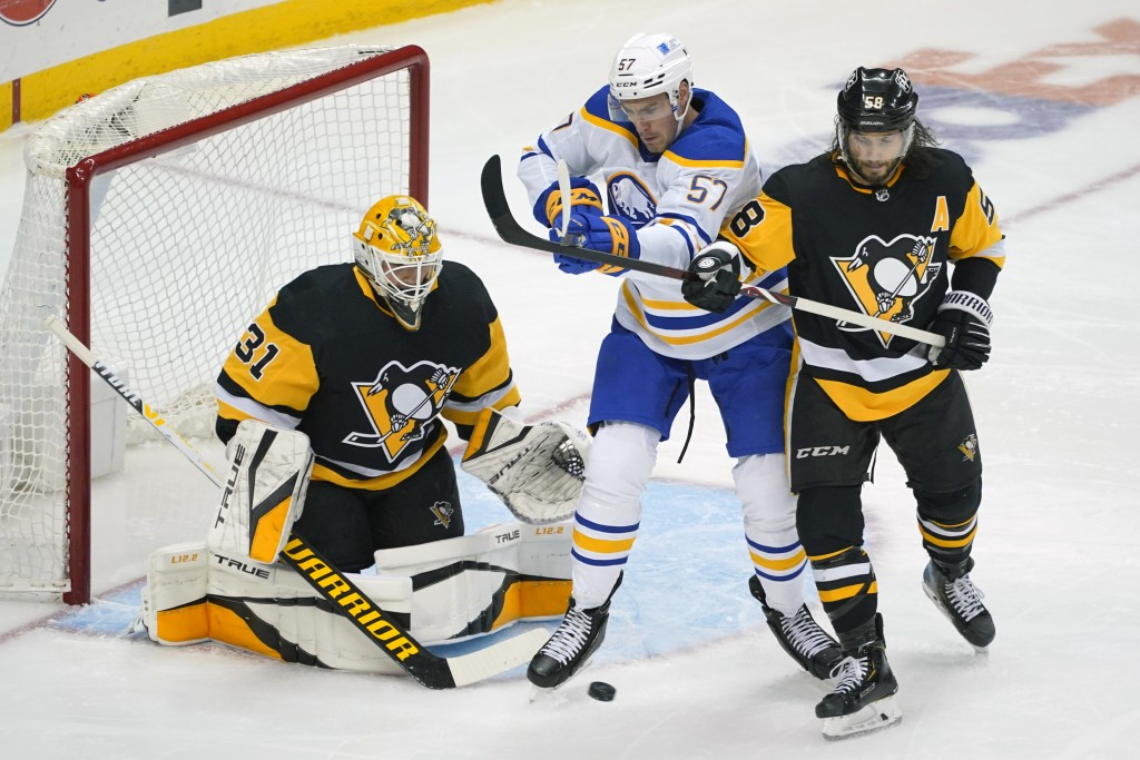 Pittsburgh Penguins' Kris Letang (58) blocks the stick of Buffalo Sabres' Brett Murray (57) in front of goaltender Maxime Lagace during the period of ...