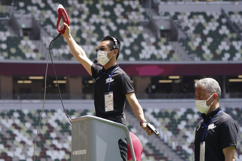 An official wearing a face mask uses a starter pistol to signal the start a women's 100 meter heat at an athletics test event for the Tokyo 2020 Olymp...