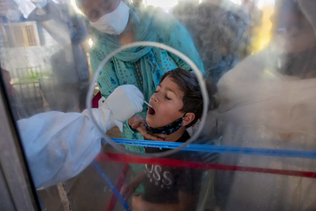 A health worker takes a mouth swab sample of a Kashmiri boy to test for COVID-19 in Srinagar, Indian controlled Kashmir, Saturday, May 8, 2021. Infect...