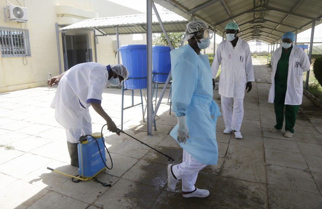 Medical personnel spray disinfectant outside the ward where COVID-19 patients are receiving treatment, at the Farcha provincial hospital in N'Djamena,...