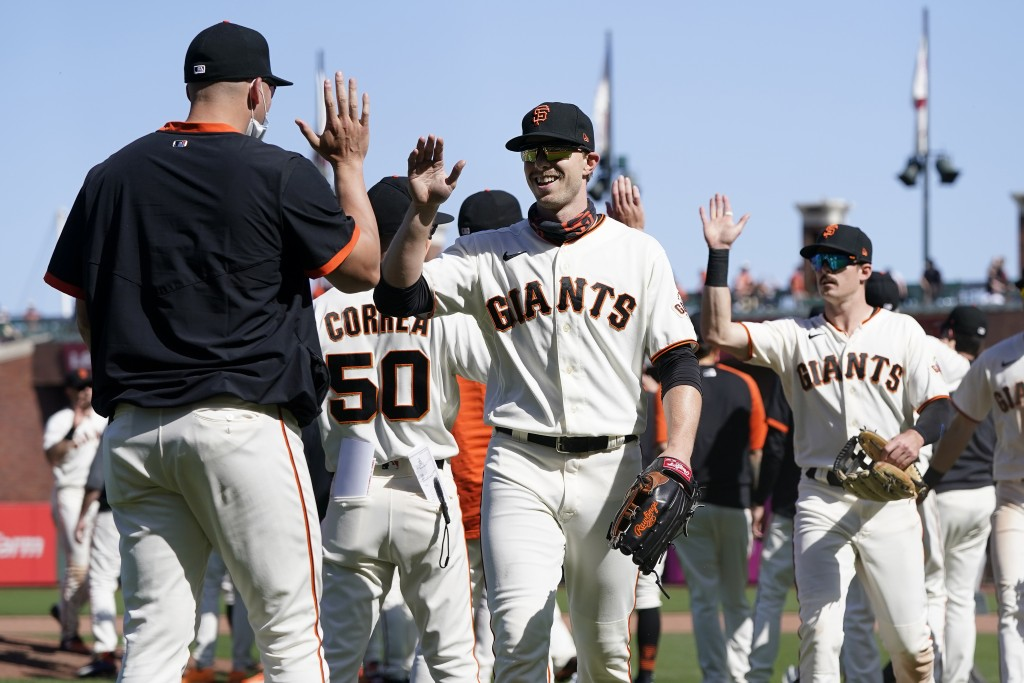San Francisco Giants' Austin Slater, middle, celebrates with teammates after the Giants defeated the San Diego Padres in a baseball game in San Franci...