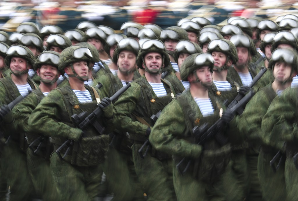 In this photo taken with long time exposure, Russian paratroopers march toward Red Square during the Victory Day military parade in Moscow, Russia, Su...