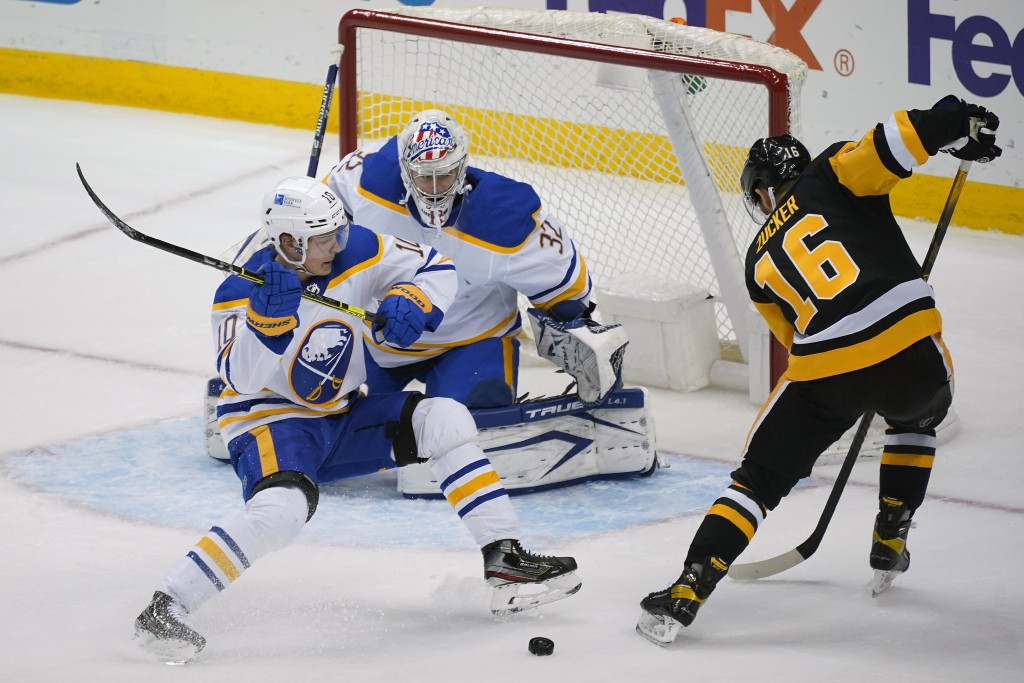 Buffalo Sabres' Henri Jokiharju (10) blocks a shot attempt by Pittsburgh Penguins' Jason Zucker (16) in front of goaltender Michael Houser during the ...