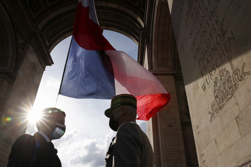 French President Emmanuel Macron, left, talks to Gen. Francois Lecointre during a ceremony at the Arc de Triomphe to mark the 76th anniversary of the ...