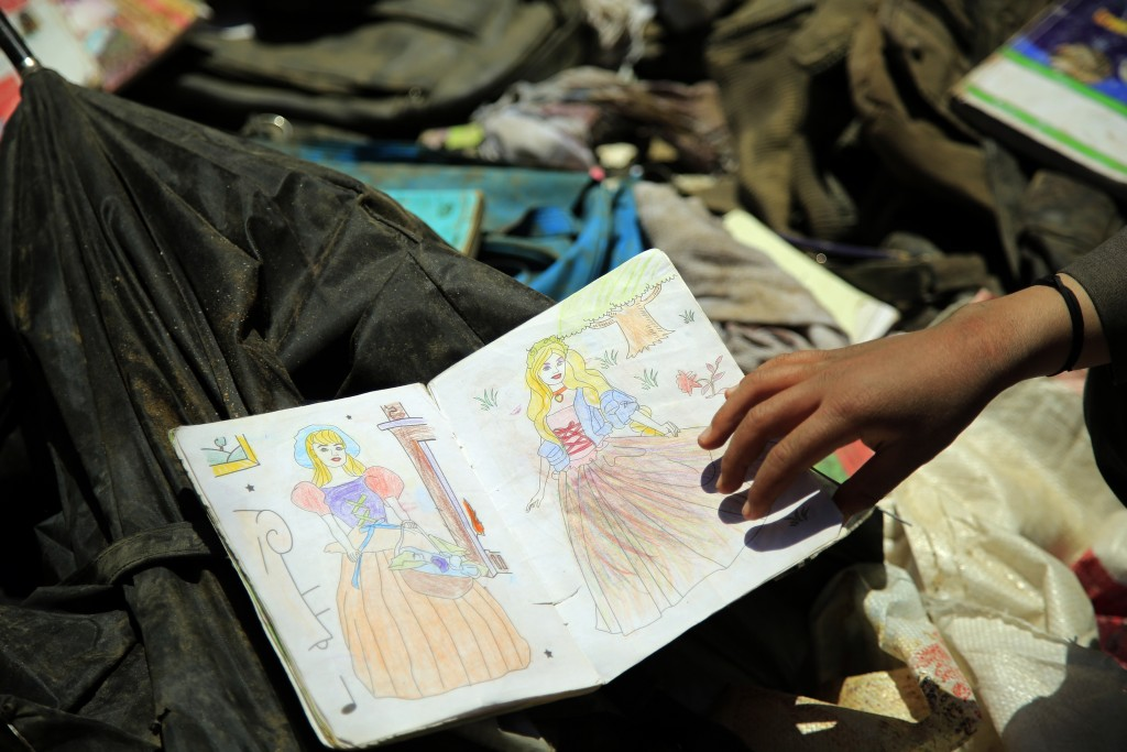 Afghans go through belongings left behind after deadly bombings on Saturday near a school, in Kabul, Afghanistan, Sunday, May 9, 2021. The Interior Mi...