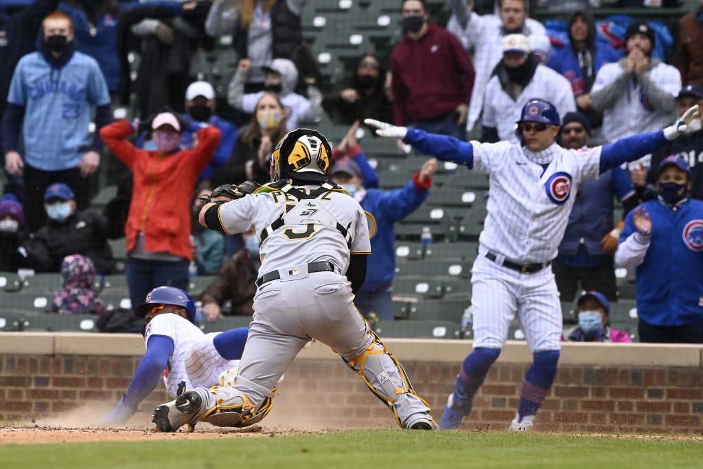 Pittsburgh Pirates catcher Michael Perez (5) looks on as Chicago Cubs' Jason Heyward (22) scores during the seventh inning of a baseball game, Saturda...