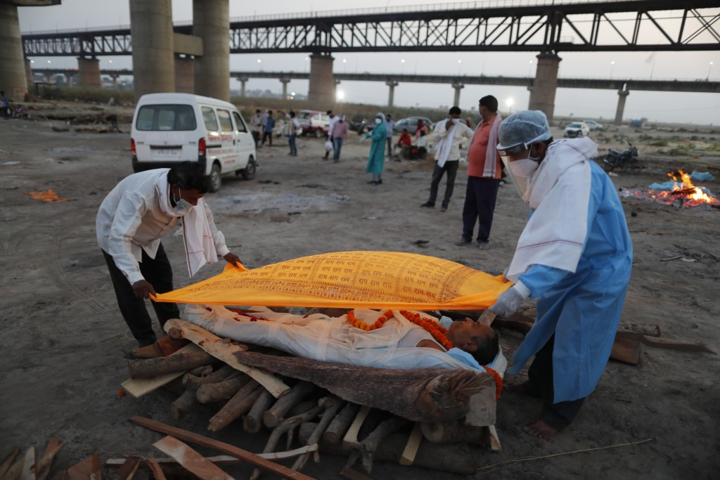 Family members place a cloth on the body of Rajendra Prasad Mishra, 62, who died due to COVID-19 before cremation by the River Ganges in Prayagraj, In...