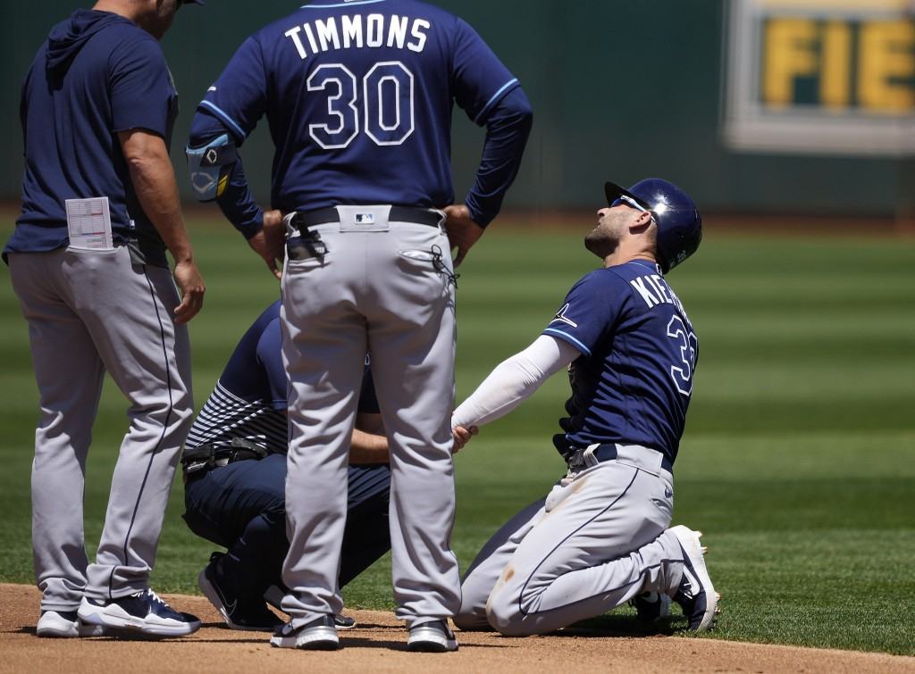 Tampa Bay Rays' Kevin Kiermaier, right, is looked at by a trainer after stealing second base during the second inning of a baseball game against the O...