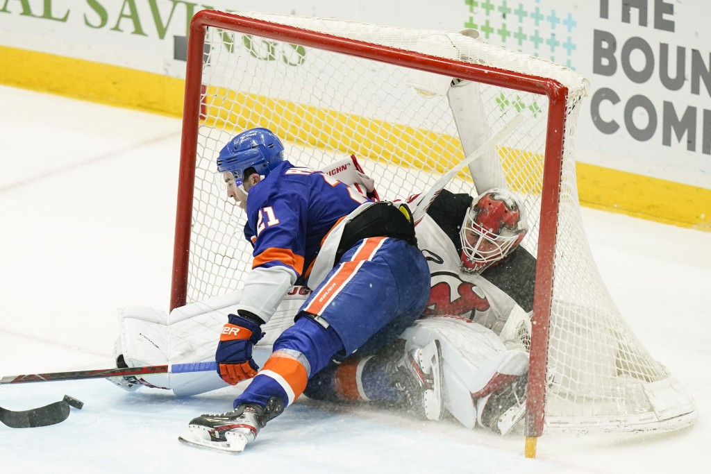 New York Islanders' Kyle Palmieri (21) crashes into New Jersey Devils goaltender Mackenzie Blackwood (29) while scoring a goal during the third period...