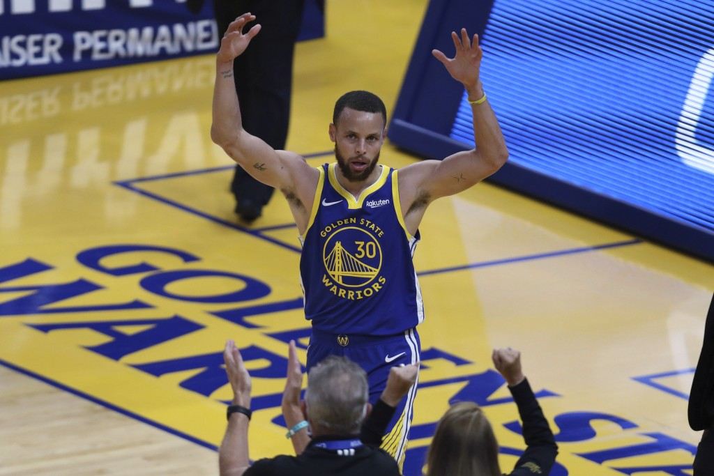 Golden State Warriors' Stephen Curry waves to the crowd after scoring against the Oklahoma City Thunder during the first half of an NBA basketball gam...