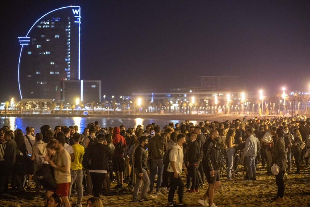 People crowded on the beach in Barcelona, Spain, Sunday, May 9, 2021. Barcelona residents were euphoric as the clock stroke midnight, ending a six-mon...