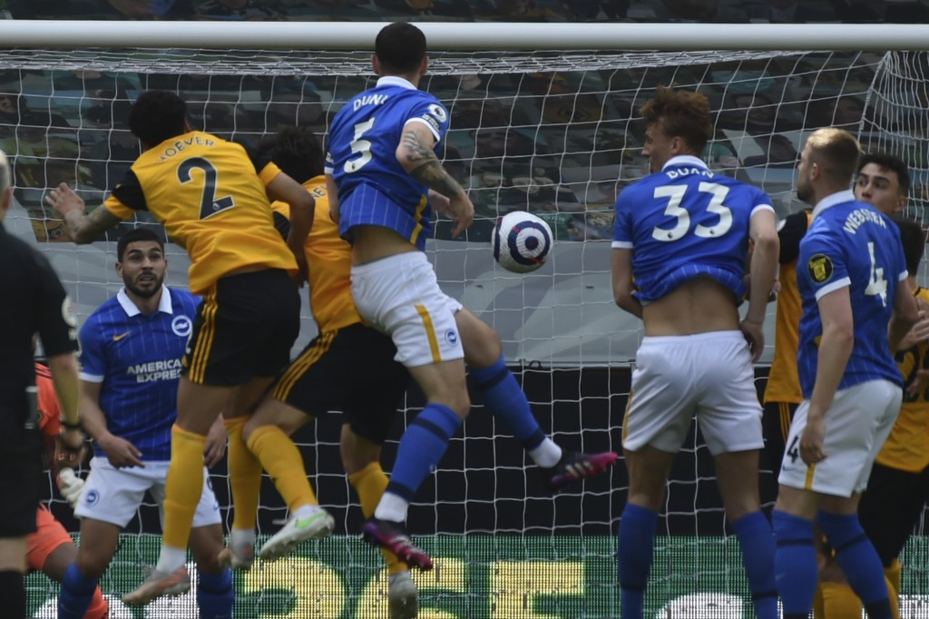 Brighton's Lewis Dunk, center, scores his side's opening goal during the English Premier League soccer match between Wolverhampton Wanderers and Brigh...