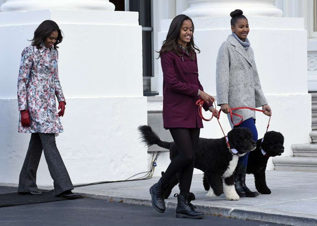 FILE - In this Nov. 28, 2014, file photo first lady Michelle Obama, left, follows her daughters Malia Obama, center, and Sasha Obama, as they arrive t...