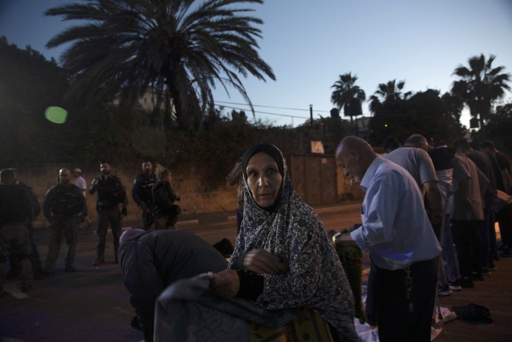 A Palestinian woman who lives in a house under threat of eviction moves prayer mats for outdoor prayers during the Muslim holy month of Ramadan, in th...
