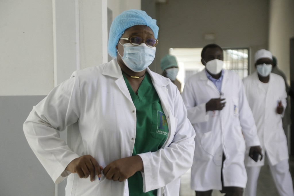 Dr. Oumaima Djarma, left, walks with other doctors dealing with COVID-19 patients, inside the Farcha provincial hospital in N'Djamena, Chad, Friday Ap...