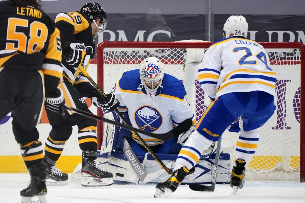 Buffalo Sabres goaltender Michael Houser blocks a shot with Pittsburgh Penguins' Jake Guentzel (59) unable to get his stick on the rebound during the ...