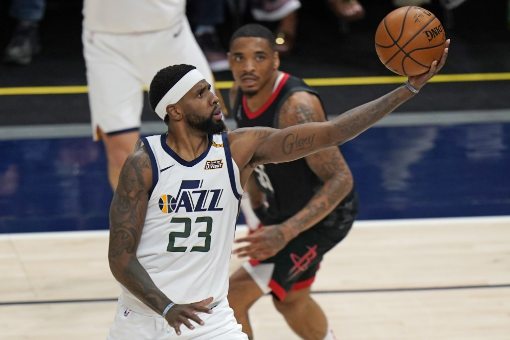Houston Rockets forward DaQuan Jeffries, rear, looks on as Utah Jazz forward Royce O'Neale (23) lays the ball up during the first half of an NBA baske...