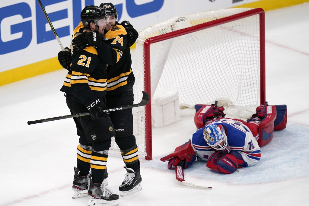 Boston Bruins left wing Nick Ritchie (21) is congratulated by Jake DeBrusk after his goal against New York Rangers goaltender Keith Kinkaid during the...