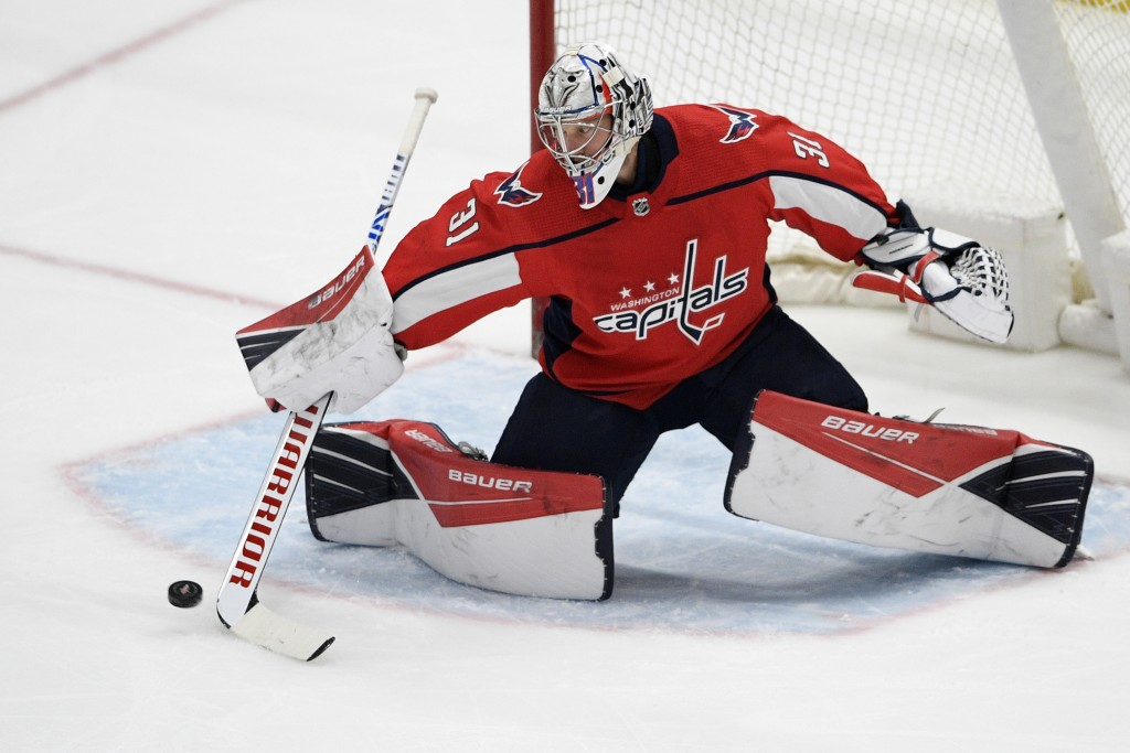 Washington Capitals goaltender Craig Anderson reaches for the puck during the first period of the team's NHL hockey game against the Philadelphia Flye...