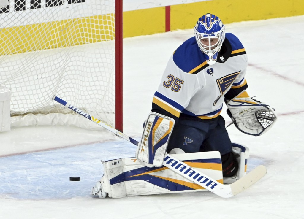 St. Louis Blues goaltender Ville Husso deflects the puck during the first period of the team's NHL hockey game against the Vegas Golden Knights on Sat...