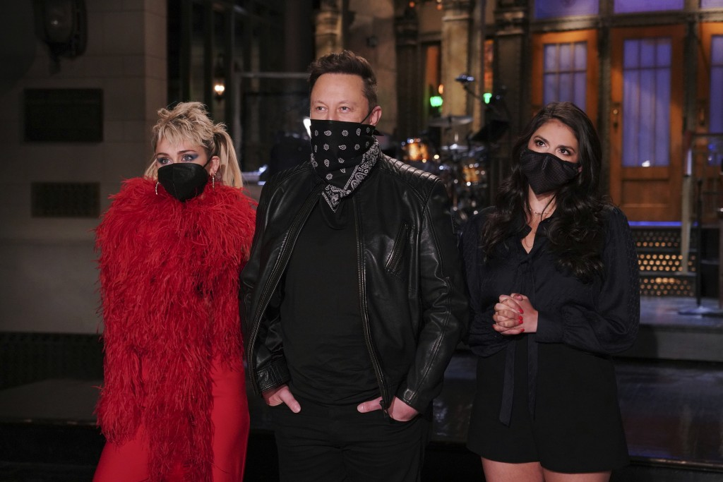 This image released by NBC shows musical guest Miley Cyrus, from left, host Elon Musk, and Cecily Strong during promos in Studio 8H on Thursday, May 6...
