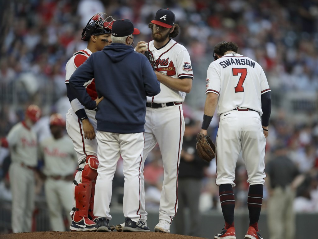 Atlanta Braves pitcher Ian Anderson, third from left, speaks with pitching coach Rick Kranitz, second from left, in the first inning of a baseball gam...