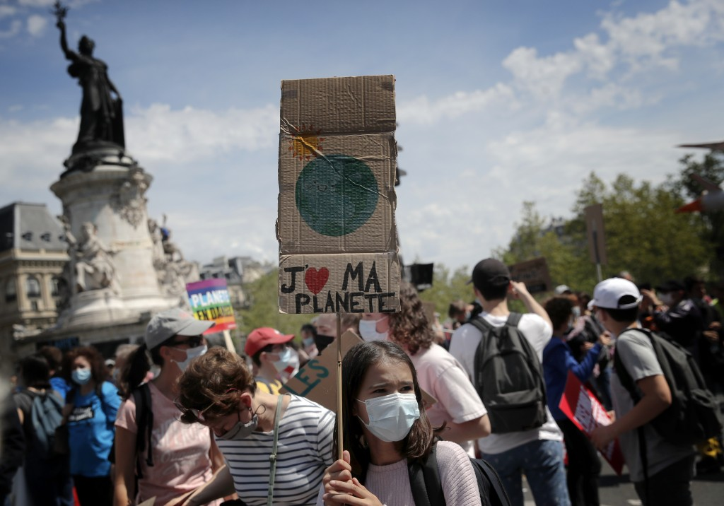 A young protester holds a bord reading «I love my planet» during a rally against the climate change in Paris, Sunday, May 9, 2021. Thousands of Fren...