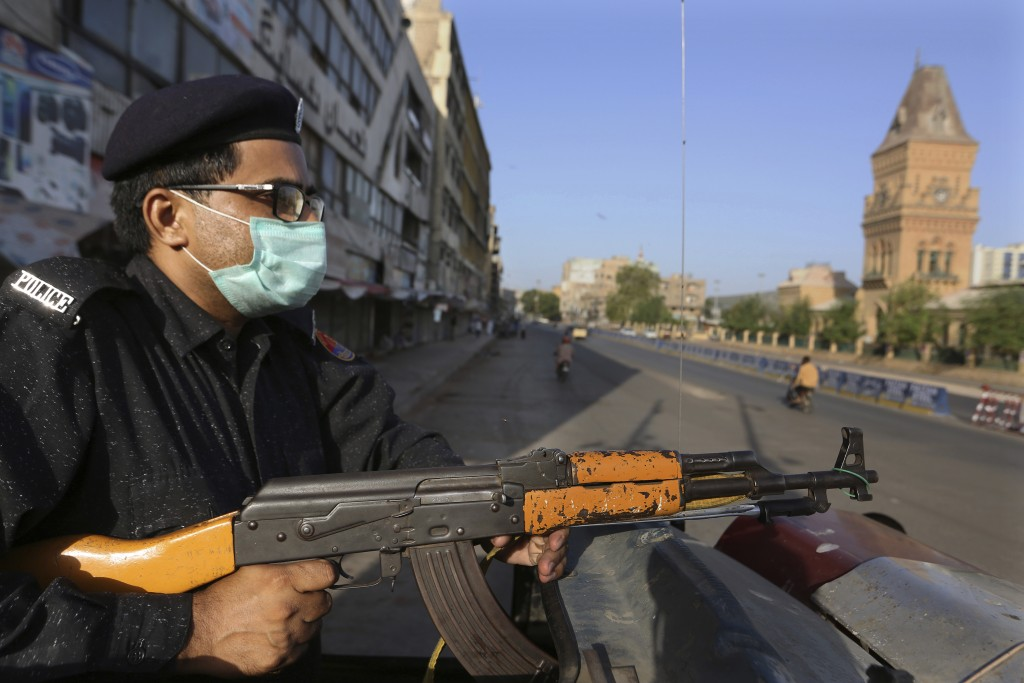 A police officer stands guard in a business district to ensure a lockdown to help control the spread of the coronavirus, in Karachi, Pakistan, Sunday,...