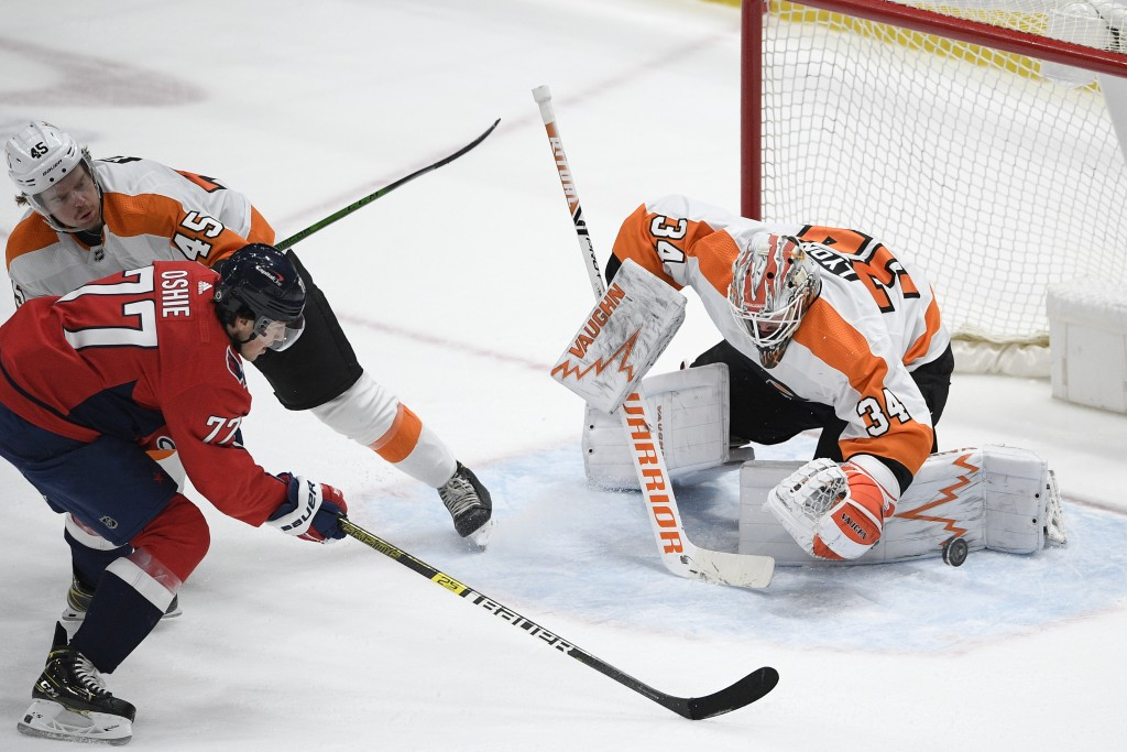 Philadelphia Flyers goaltender Alex Lyon (34) stops the puck against Washington Capitals right wing T.J. Oshie (77) during the second period of an NHL...