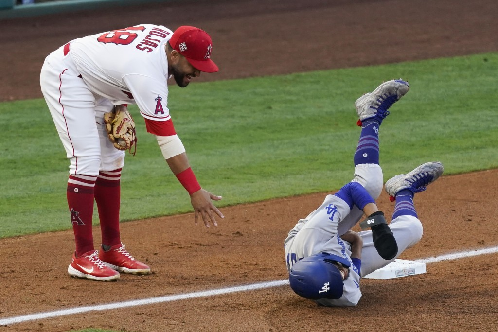 Los Angeles Dodgers' Mookie Betts (50) reacts after Los Angeles Angels third baseman Jose Rojas (18) hit him in the groin area as Rojas caught a ball ...