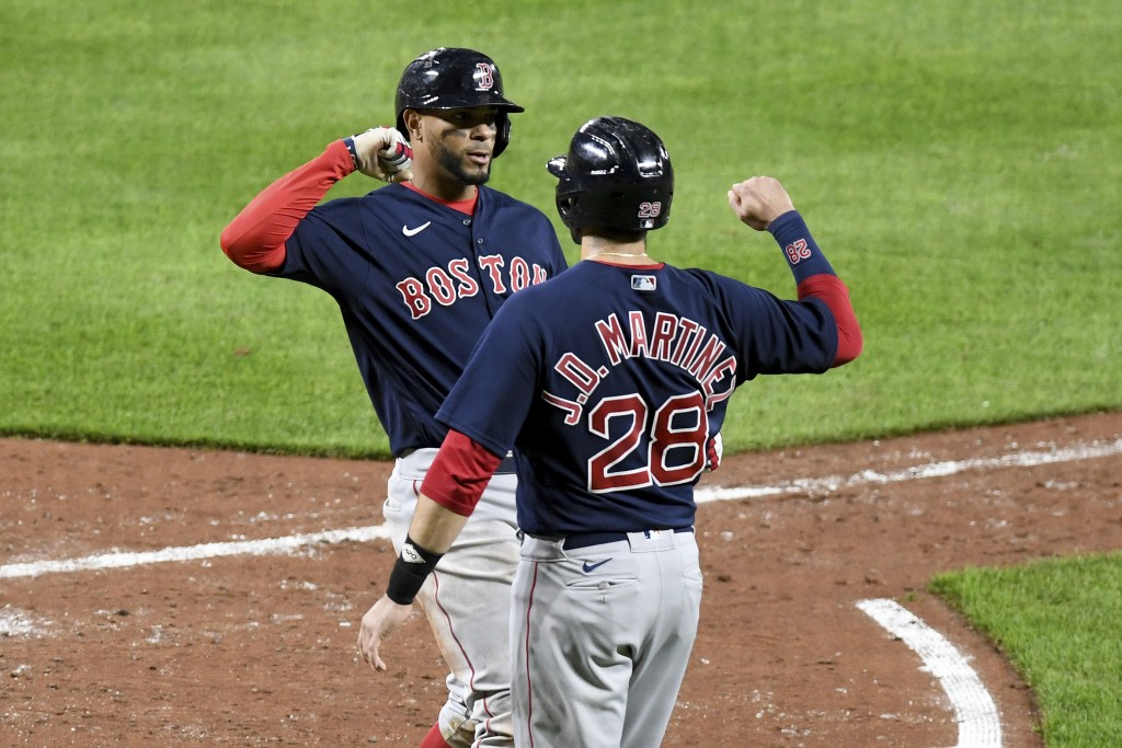 Boston Red Sox's Xander Bogaerts celebrates with teammate J.D. Martinez (28) after hitting a two-run home run against the Baltimore Orioles in the six...