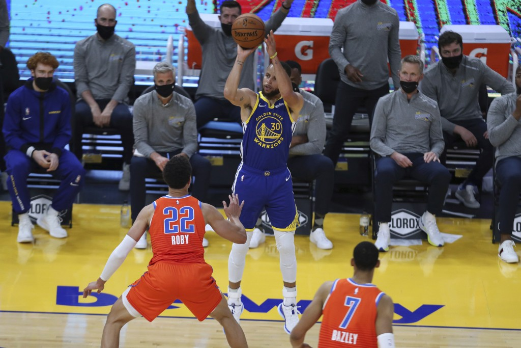 Golden State Warriors' Stephen Curry, center, shoots a 3-pointer against Oklahoma City Thunder's Isaiah Roby during the first half of an NBA basketbal...