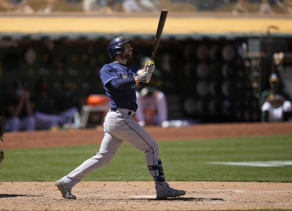 Tampa Bay Rays' Brandon Lowe watches the flight of his two-run home run during the sixth inning of a baseball game against the Oakland Athletics, Satu...