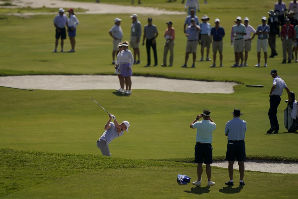 Jack Dyer, of the Great Britain and Ireland team, hits from the bunker on the 12th hole in the foursome matches during the Walker Cup golf tournament ...