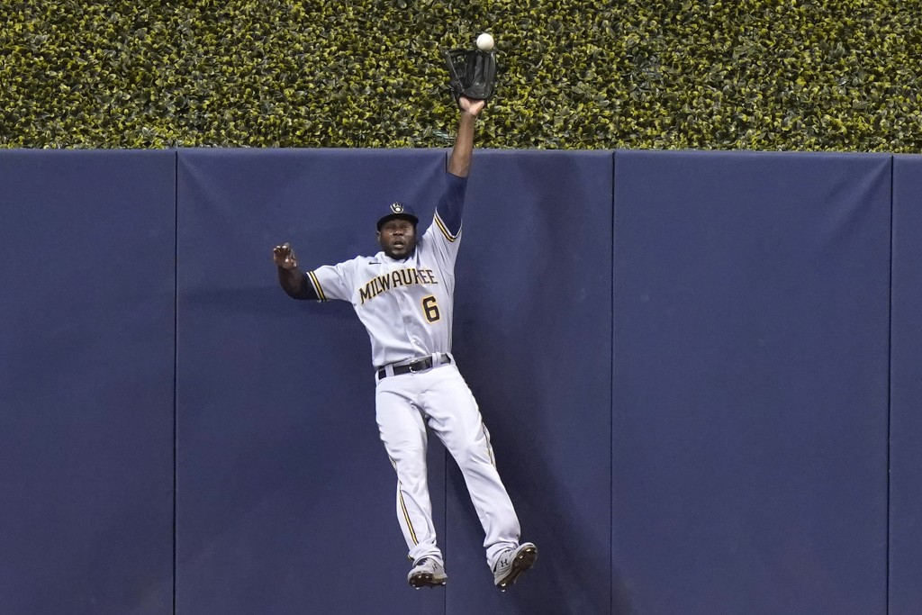 Milwaukee Brewers center fielder Lorenzo Cain (6) can't make the catch on a solo home run hit by Miami Marlins' Miguel Rojas during the first inning o...