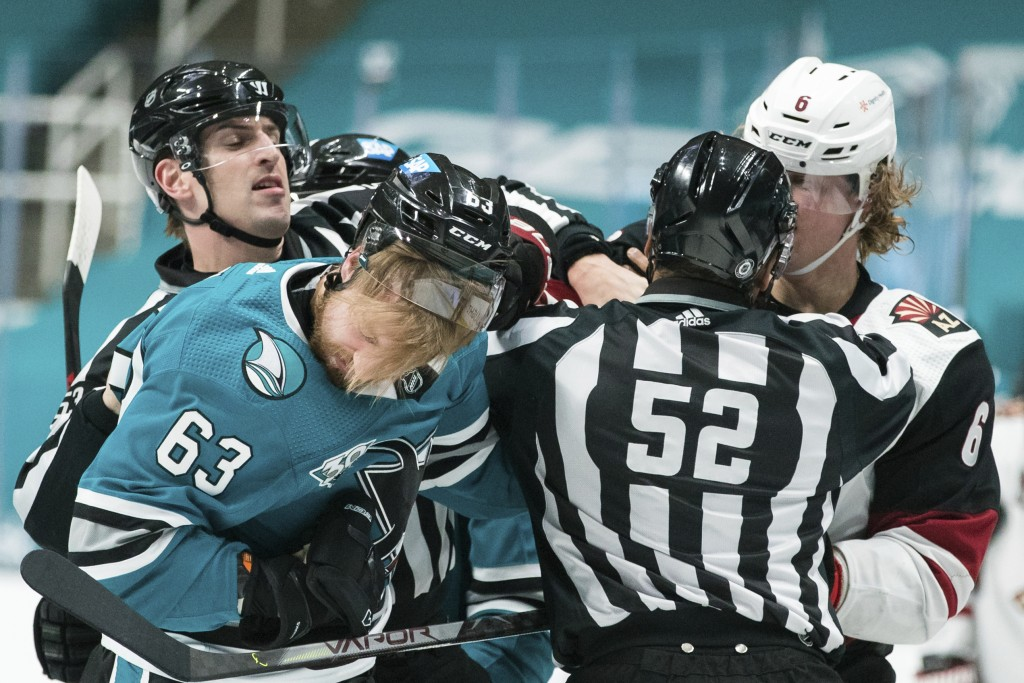 San Jose Sharks left wing Jeffrey Viel (63) and Arizona Coyotes defenseman Jakob Chychrun (6) fight during the first period of an NHL hockey game in S...
