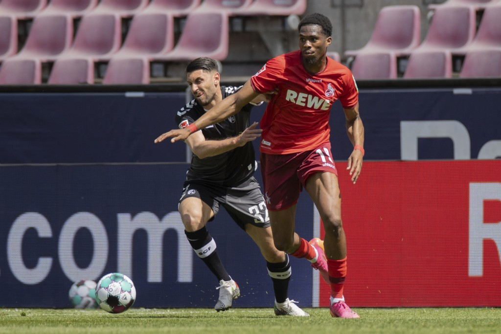 Cologne's Kingsley Ehizibue, left, and Freiburg's Vincenzo Grifo, right, challenge for the ball during the German Bundesliga soccer match between 1. F...