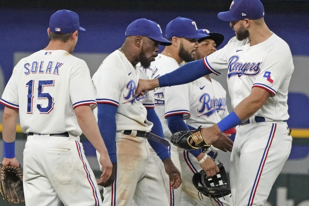 Texas Rangers center fielder Adolis Garcia, second from left, absorbs a playful punch from teammate Joey Gallo, right, as they celebrate their win ove...
