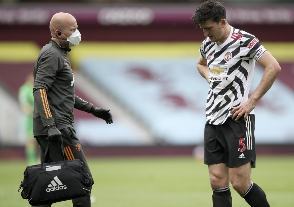 Manchester United's Harry Maguire, right, leaves the field with medics during the English Premier League soccer match between Aston Villa and Manchest...