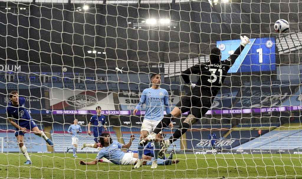 Chelsea's Marcos Alonso, left, scores the winning goal during the English Premier League soccer match between Manchester City and Chelsea at the Etiha...