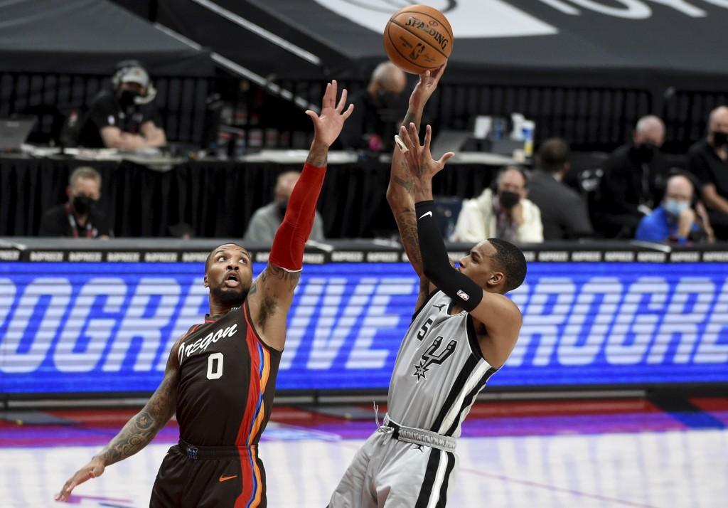 San Antonio Spurs guard Dejounte Murray, right, shoots over Portland Trail Blazers guard Damian Lillard during the first half of an NBA basketball gam...