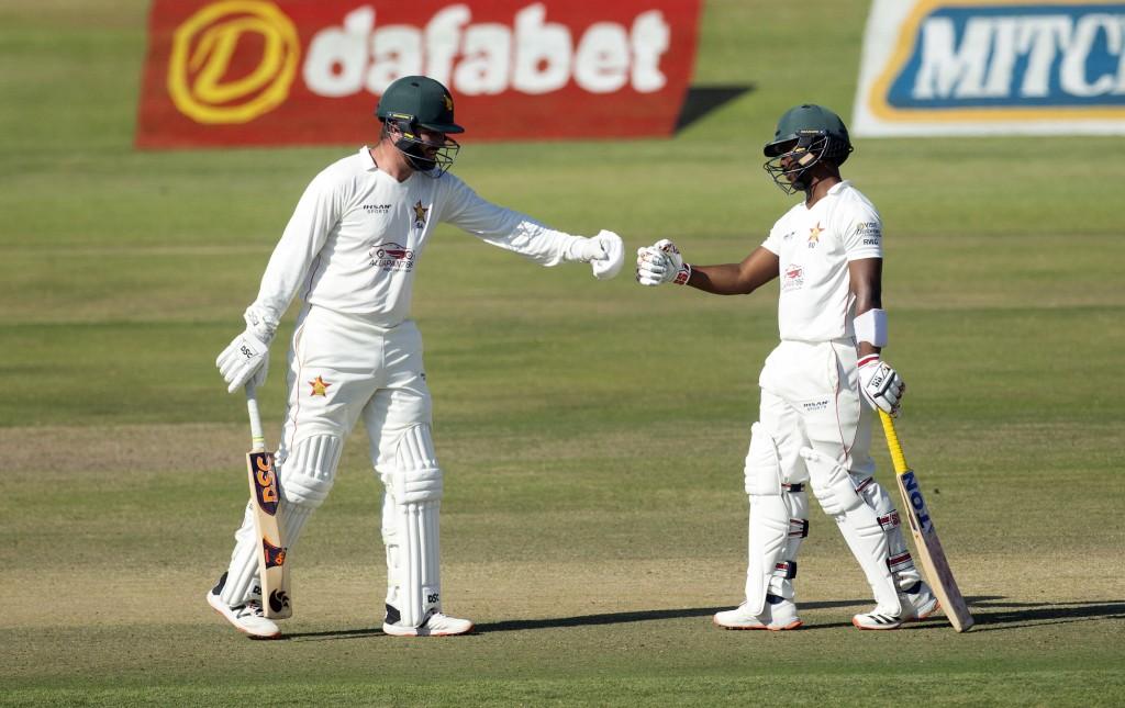 Zimbabwean batsmen Brendan Taylor,left and Regis Chakabva touch gloves during the second test cricket match against Pakistan at Harare Sports Club, Su...