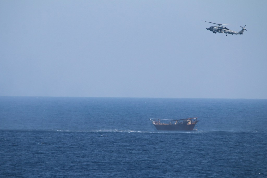 A U.S. Navy Seahawk helicopter flies over a stateless dhow later found to be carrying a hidden arms shipment in the Arabian Sea on Thursday, May 6, 20...