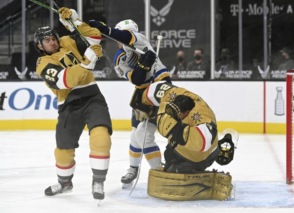 Vegas Golden Knights goaltender Marc-Andre Fleury (29) has his helmet knocked off by defenseman Alec Martinez (23) and St. Louis Blues left wing Macke...