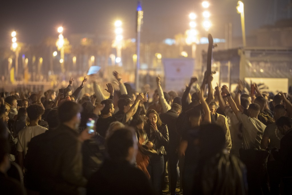 People crowded and dance on the beach in Barcelona, Spain, Sunday, May 9, 2021. Barcelona residents were euphoric as the clock stroke midnight, ending...