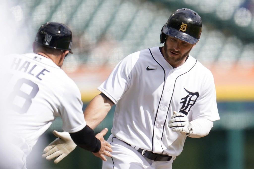 Detroit Tigers left fielder Robbie Grossman, right, celebrates his solo home run with third base coach Chip Hale (18) against the Minnesota Twins in t...