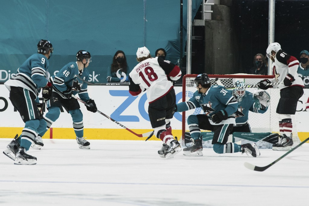 Arizona Coyotes center Christian Dvorak (18) scores a goal against the San Jose Sharks during the first period of an NHL hockey game in San Jose, Cali...