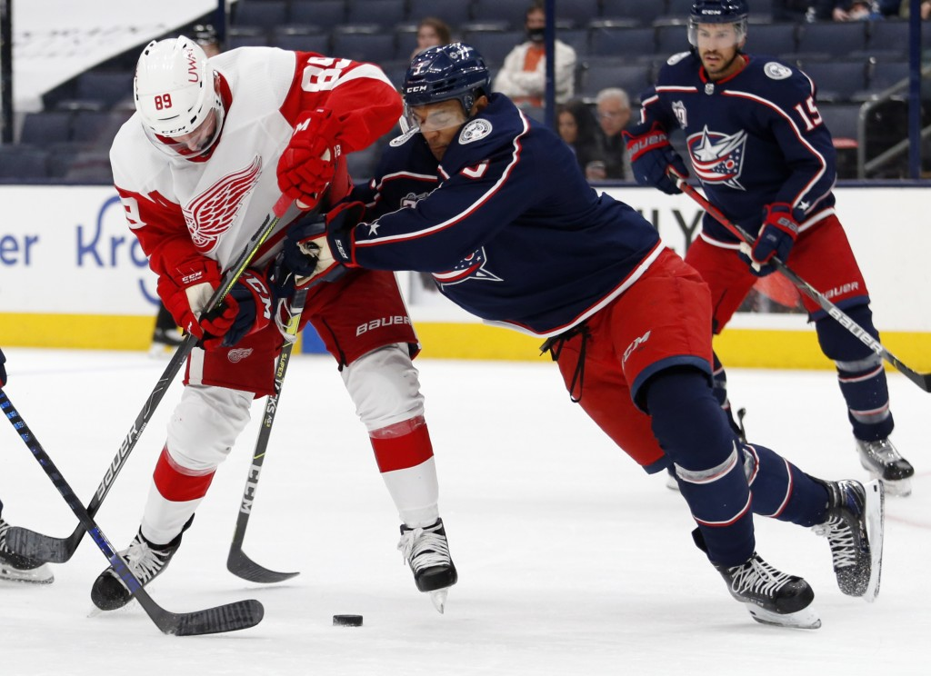 Columbus Blue Jackets defenseman Seth Jones, front right, checks Detroit Red Wings forward Sam Gagner during the first period of an NHL hockey game in...