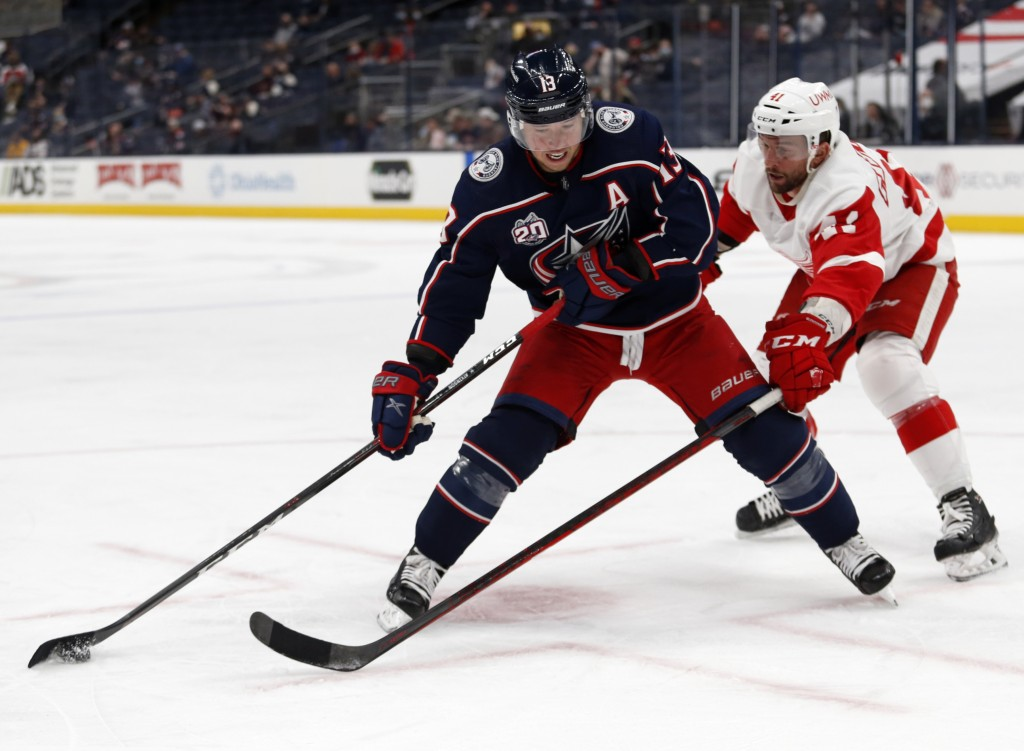 Columbus Blue Jackets forward Cam Atkinson, left, controls the puck in front of Detroit Red Wings forward Luke Glendening during the second period of ...