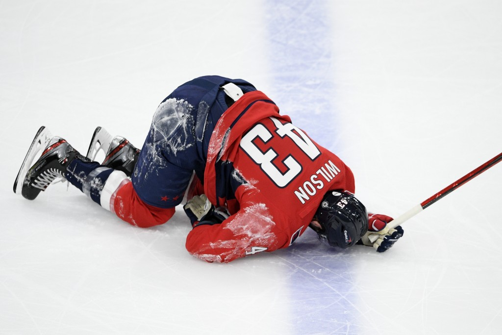 Washington Capitals right wing Tom Wilson lies on the ice after he was injured during the first period of the team's NHL hockey game against the Phila...